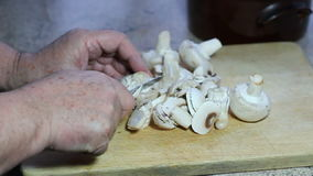 Slicing mushrooms on a wooden board. stock footage