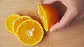 Slicing an orange fruit on a kitchen cutting Board, wooden table as background, close view.