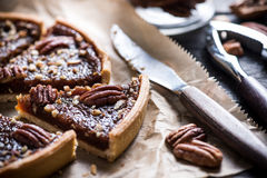 Slicing pecan pie, on wooden table Stock Photography