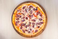 Slicing pizza with smoked sausage, ham and cheese. Close-up view. royalty free stock images