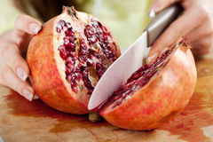 Slicing pomegranate Stock Photo