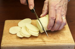 Slicing a potato Royalty Free Stock Photos