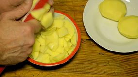 Slicing the potatoes before cooking. Human hands or chef slice up raw yellow potatoes with a red kitchen knife. Close-up stock video footage