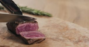 Slicing rare fillet mignon steak on wood board. Wide photo stock image