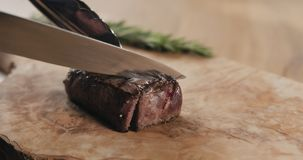 Slicing rare fillet mignon steak on wood board. Wide photo royalty free stock images