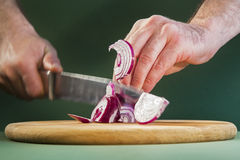 Slicing red onion on cutting board. Stock Images