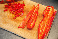 Slicing red sweet peppers Royalty Free Stock Photo