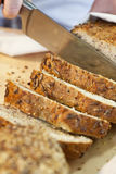 Slicing Rustic Wholemeal Seeded Loaf of Bread Stock Photography