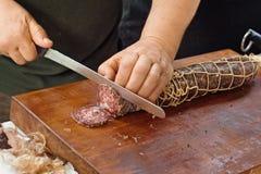 Slicing salami royalty free stock image