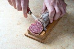 Slicing salami royalty free stock photo