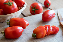 Slicing San Marzano tomatoes on a cutting board.  Royalty Free Stock Images