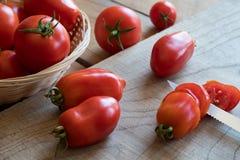 Slicing San Marzano tomatoes on a cutting board. Slicing freshly harvested San Marzano tomatoes on a cutting board Stock Photo