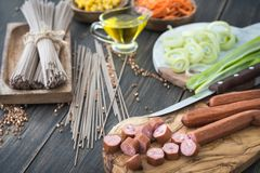 Slicing sousages for soba noodles cooking with leek, corn and ko Royalty Free Stock Image