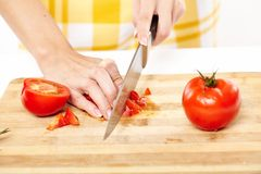 Slicing the tomato on a wooden board Stock Photography