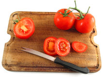 Slicing tomatoes. Sliced, juicy tomatoe on wooden plate (up view Stock Photos