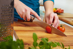 Slicing tomatoes on carving board Stock Photos
