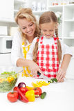 Slicing vegetables in kitchen Stock Image