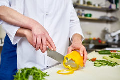 Slicing vegetables. Trainee and chef slicing ingredients for salad Royalty Free Stock Image