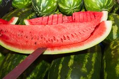 Slicing a watermelon on an open air market stand Stock Photos