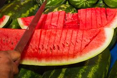 Slicing a watermelon on an open air market stand Royalty Free Stock Photography