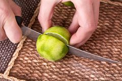 Slicing zested lime with knife. Royalty Free Stock Images