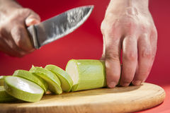 Slicing zucchini on cutting board. Stock Photography