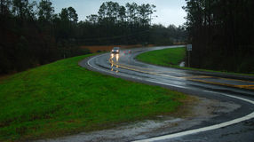 Slick S Curve. Car with headlights maneuvering rain slick S curve Royalty Free Stock Photography