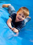 Slide. Happy little boy sliding on a bright blue slide Stock Images