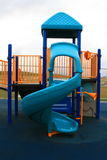 Slide. Blue slide in a school playground in a summer Royalty Free Stock Image