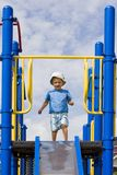 Slide. Boy stands looking down from top of slide at playground stock image