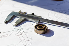 Slide caliper and ball bearing lie on a drawings Royalty Free Stock Photography