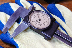Slide caliper with round dial on a working glove Royalty Free Stock Photos