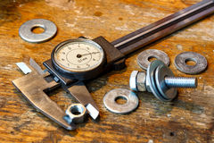 Slide caliper with round scale and bolt with nuts on the workbench in workshop Royalty Free Stock Photo