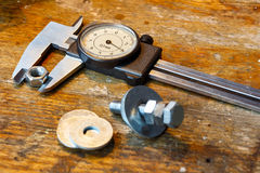 Slide caliper with round scale and bolt with nuts on the workbench in workshop stock images