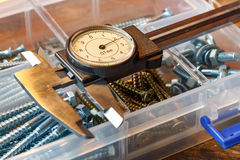 Slide caliper with round scale and screws in storage box on a wooden table Stock Images