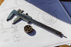 Slide caliper and used ball bearing on the background of drawings Royalty Free Stock Photos