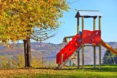Slide on empty playground. Lone children's slide on empty playground in autumn in small town of Diano D'Alba, Italy Stock Photos