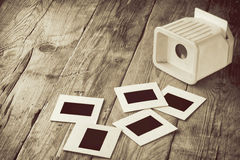 Slide film is scattered on old wooden table Royalty Free Stock Images