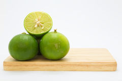 Slide fresh green limes on wooden board Royalty Free Stock Photo