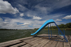 Slide on the lake dock. With cloudy sky Royalty Free Stock Image