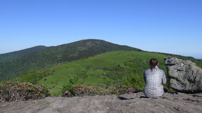 Slide Left Behind Woman Sitting on Jane Bald Rocks during rhododendron bloom in June stock footage