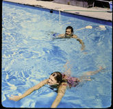 Slide 35 mm to photograph. Taken in back yard pool in late 1960`s. Slide 35 mm to photograph. Couple swimming in pool circa 1960`s in California Royalty Free Stock Photos