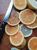 Slide orange and lemon. Orange and lemon cut into slides of bright and suggestive colors on wooden board royalty free stock photography