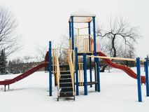 The slide in the playground is very big. It is snowing ,this is the slide on the playground of my apartment Royalty Free Stock Photography