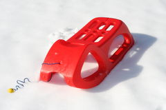 Slide red used to play and to descend from the mountains. Plastic slide red used to play and to descend from the mountains with snow Stock Image
