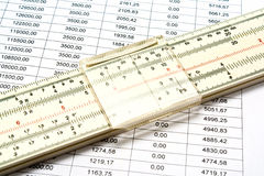 Slide rule. Old slide rule lying on sheet with figures Royalty Free Stock Image