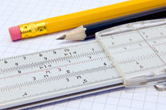 Slide rule. And pencils on a gridded paper Stock Photography