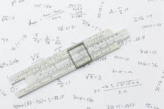 Slide rule and calculations. Slide rule lying on a piece of paper with handwritten calculations Royalty Free Stock Image