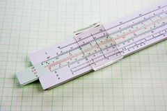 Slide rule on squared paper Royalty Free Stock Image