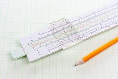Slide rule on squared paper with wooden pencil Royalty Free Stock Photography